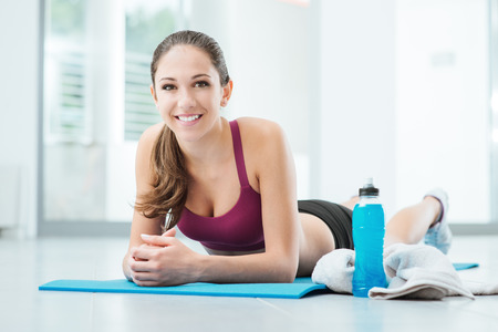 lying down: Smiling young woman relaxing after workout, she is resting belly down on a mat and looking at camera