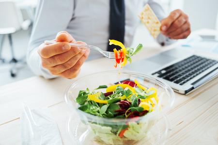 Zakenman met een lunchpauze op het bureau, hij is het eten van verse salade en houden van een cracker, onherkenbaar persoon Stockfoto