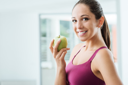 Young slim woman holding an apple and smiling at camera, healthy eating and weight loss concept