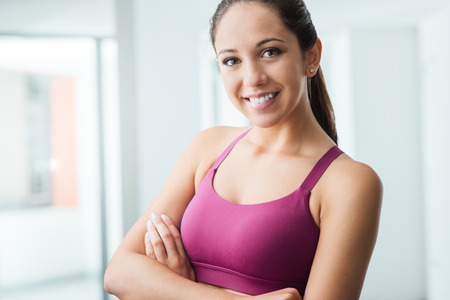 healthy looking: Young smiling woman posing at the gym and looking at camera, fitness and healthy lifestyle concept Stock Photo