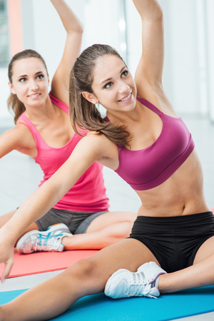 Smiling happy girls doing stretching exercises during a class at the gym, fitness and workout concept photo