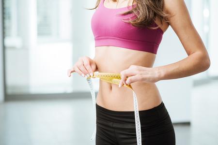vientre femenino: Mujer joven delgada que mide su cintura fina con una cinta métrica, de cerca