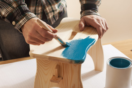 footstool: Craftsman varnishing a wooden handmade stool at home with a blue coating on a work table, hands close up