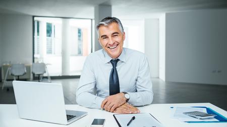 Magabiztos jóképű üzletember ül íróasztal és mosolygós, fényképezőgép