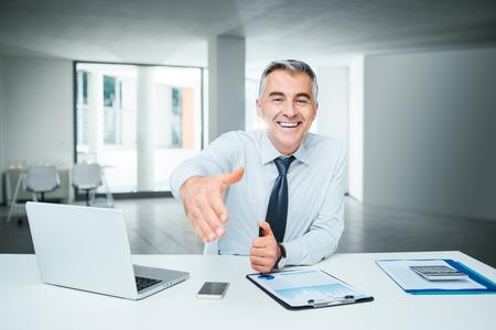 contrato de trabajo: Sonriente hombre de negocios confía en dar un apretón de manos, el acuerdo y el concepto de contratación Foto de archivo