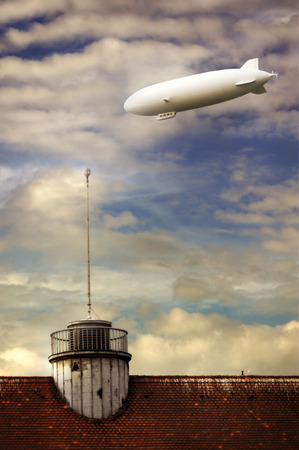 blimp: a blimp flies over the city against a dramatic sky full of clouds at sunset