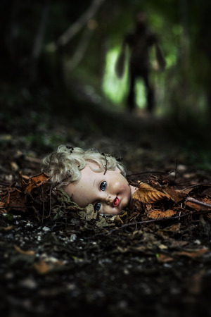presence: A dolls head lying in the middle of a path of a dark forest. There is a haunting presence in the background blurred.