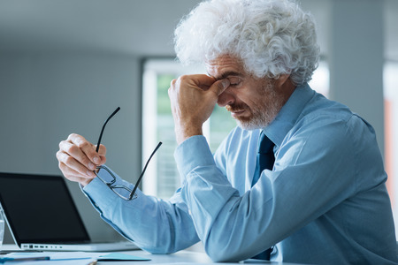 Stressed exhausted businessman sitting at office desk, failure and loss concept