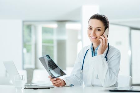 Lachende vrouwelijke arts aan de telefoon in het kantoor bedrijf medische dossiers en praten met een patiënt