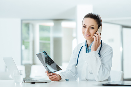 on call: Smiling female doctor on the phone in the office holding medical records and talking with a patient