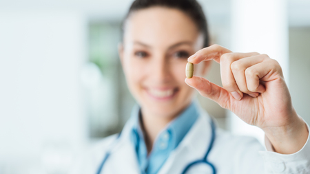 Smiling female pharmacist holding a pill, health care and prevention concept, hand close up