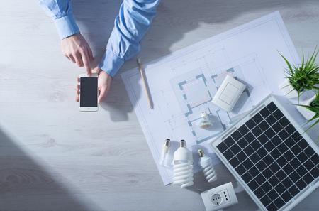 男は携帯電話を使ってタッチ画面スマート フォン ソーラー パネルの横にある、CFL ランプ、家プロジェクト、省エネルギー概念のセット