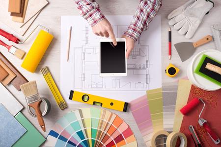 herramientas de trabajo: decorador profesional utilizando una tableta digital, herramientas de trabajo, rodillos de pintura y muestras de color por todas partes, vista desde arriba