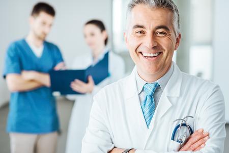 grupo de médicos: Doctor confidente posando y sonriendo a la cámara y el personal médico comprobando los registros médicos en el fondo