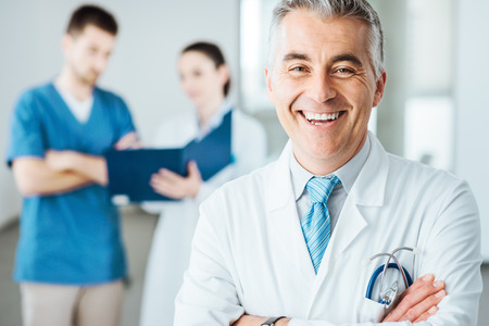 Confident doctor posing and smiling at camera and medical staff checking medical records on background Stockfoto