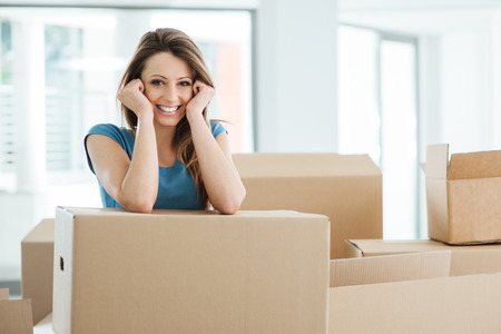 moving box: Smiling young woman moving in her new house and leaning on a cardboard box