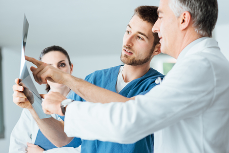 Professional medical team with doctors and surgeon examining patient's x-ray image, discussing and pointing