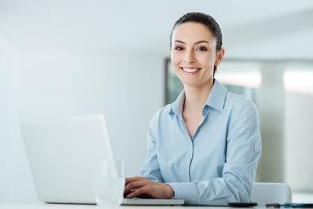 typing: joven empresaria de trabajo en el escritorio de oficina y escribir en un ordenador portátil sonriente, ella está mirando a la cámara