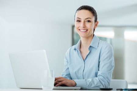 woman white shirt: Smiling young businesswoman working at office desk and typing on a laptop, she is looking at camera