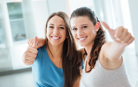 enjoyment: Cheerful teenager girls thumbs up smiling at camera, youth and enjoyment concept