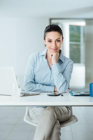 Mooie zekere vrouwelijke manager zitten aan een bureau en lacht naar de camera met de hand op de kin, kamer interieur op de achtergrond Stockfoto