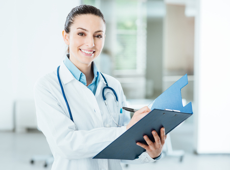 Smiling female doctor with lab coat in her office holding a clipboard with medical records, she is looking at camera Stockfoto