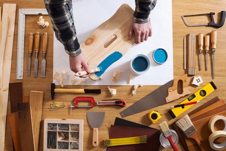 herramientas de trabajo: Decorador barnizar un taburete de madera con una capa azul sobre una mesa de trabajo con herramientas de bricolaje en todo, vista superior