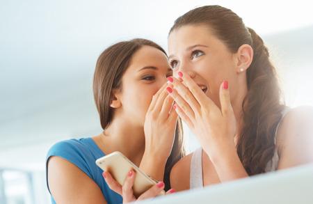 Les jeunes filles bavardent et amusent, on chuchote à l'oreille de son ami un secret