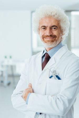 pathologist: Confident doctor at hospital posing with folded arms and smiling at camera