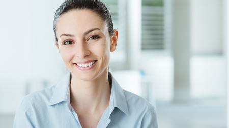 woman white shirt: Beautiful young smiling business woman smiling and looking at camera, office interior on background