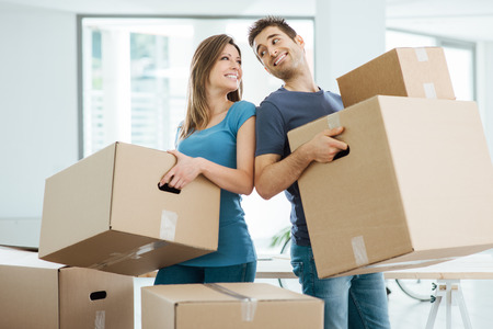 carrying: Happy couple staring at each other eyes and carrying boxes in their new house