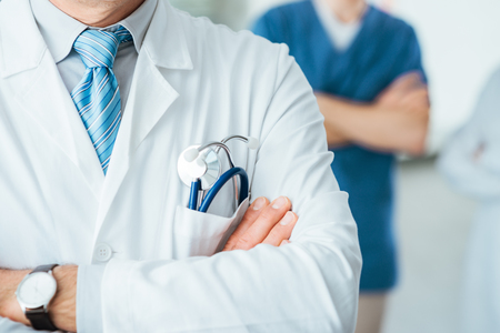 Professional medical team posing, doctor's lab coat and stethoscope close up, selective focus