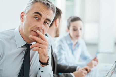üzlet: Magabiztos szakmai üzletember, mosolygós, fényképezőgép, irodai és üzleti csapat dolgozik a háttérben, szelektív összpontosít