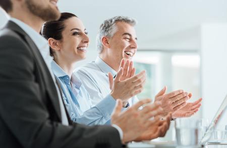 Vrolijk lachende mensen uit het bedrijfsleven de handen klappen tijdens een seminar, succes en prestatie concept