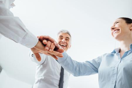 manos juntas: Personas alegres del apilamiento manos y sonriendo, trabajo en equipo y el concepto de éxito, las manos se cierran para arriba