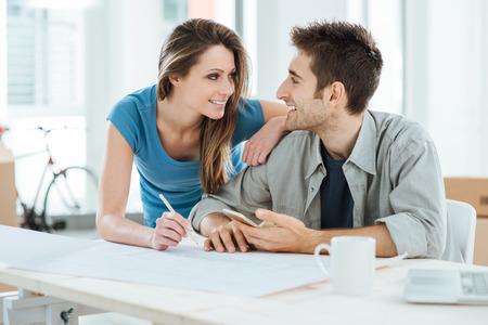 pareja en casa: Romántica pareja amorosa planificación y el diseño de su nueva casa, ellos están mirando a los ojos del otro