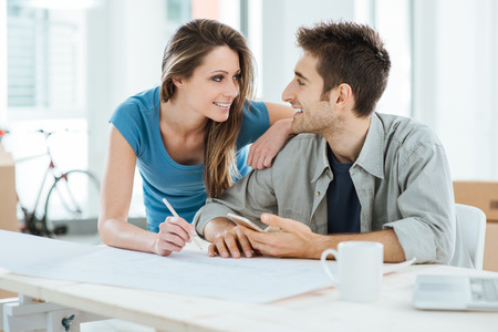 home planning: Romantic loving couple planning and designing their new house, they are staring at each others eyes Stock Photo