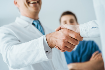 doctor of medicine: Professional doctors handshaking at hospital, hands close up, agreement and hiring concept Stock Photo
