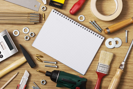 home improvement: Home DIY and improvement concept, blank notebook with work tools all around on a wooden table, top view