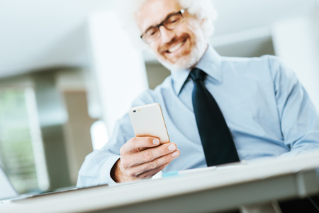 Smiling businessman sitting at office desk and using a touch screen smart phone, texting and networking online Stok Fotoğraf