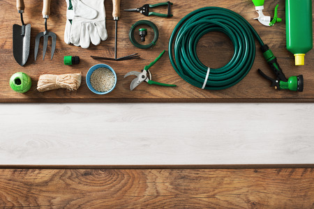 Gardening and farming tools on a wooden table and blank copy space, top view