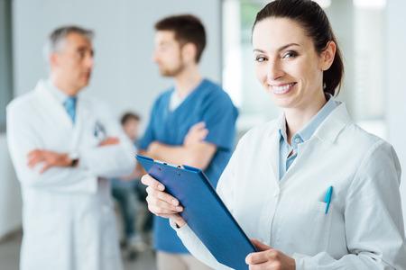 personal medico: Profesional médico mujer sonriendo a la cámara y posando, el personal médico que trabaja en el fondo, el enfoque selectivo