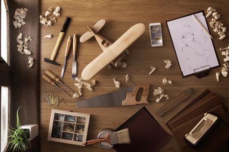 DIY project thuis concept, werktafel met handgemaakte houten speelgoed vliegtuig en timmerwerk werkgereedschap, bovenaanzicht Stockfoto