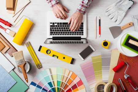typing: Manos del decorador profesional que trabaja en su escritorio y escribiendo en un ordenador portátil, muestras de color, los rodillos de pintura y herramientas sobre la mesa de trabajo, vista desde arriba
