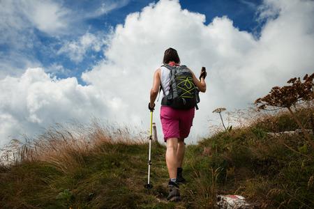 persona caminando: Mujer de senderismo con bastones de senderismo, nordic walking y deportes al aire libre concepto Foto de archivo