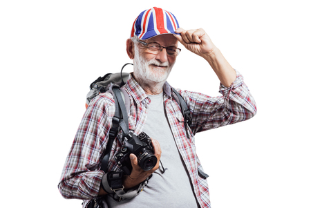 british: Senior photographer and adventurer posing with backpack and digital camera, he is touching his British flag cap
