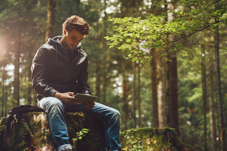 Young handsome man sitting in the woods and using a digital touch screen tablet, wi-fi connection and freedom concept Stock Photo