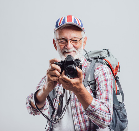 a hobby: Senior tourist photographer with backpack and digital camera, he is wearing a British flag cap