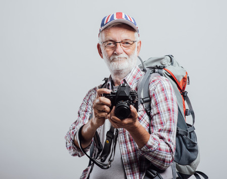 photography: Senior tourist photographer with backpack and digital camera, he is wearing a British flag cap