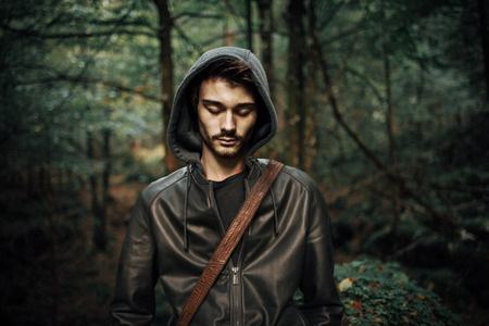 man looking: Young hooded cool man in the woods looking down, wild forest on background Stock Photo